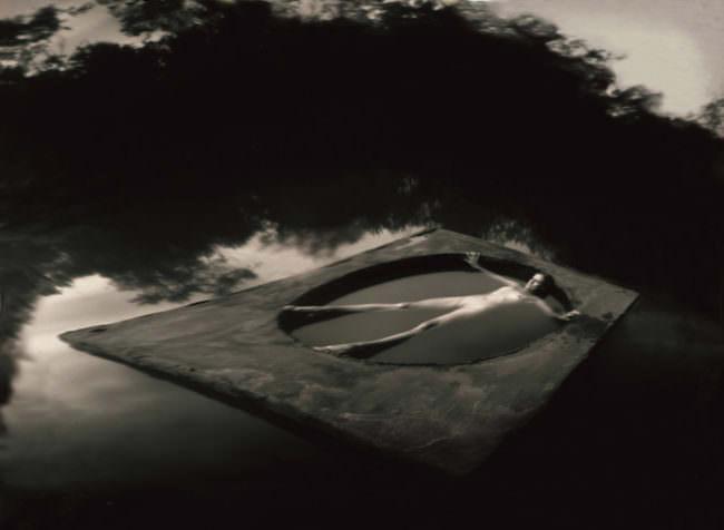 Nackte Frau in einem geometrischen Gebilde auf der Oberfläche eines Sees treibend.