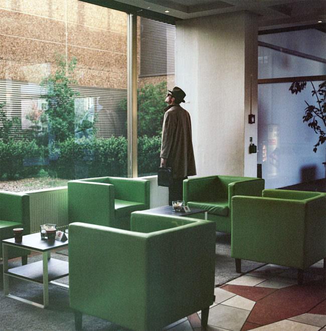 Ein Mann mit Mantel und Aktentasche steht vor einer großen Fensterfront
