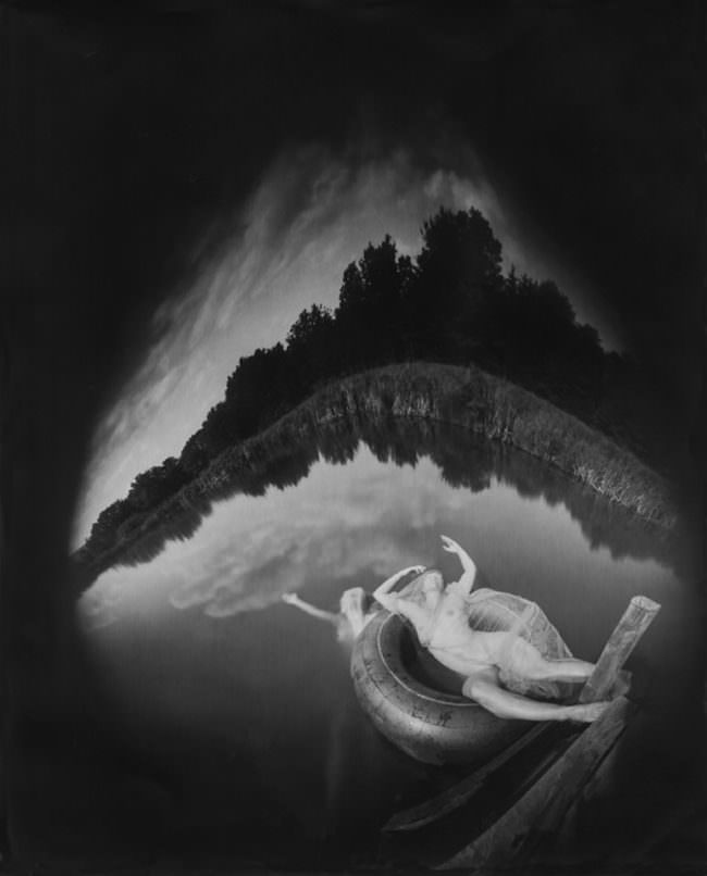 Nackte Frauen in einem See mit verzerrtem Horizont. Eine im Wasser, die andere liegend auf einem Schwimmring.