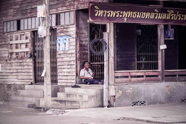 Ein Mann liest vor einem Haus