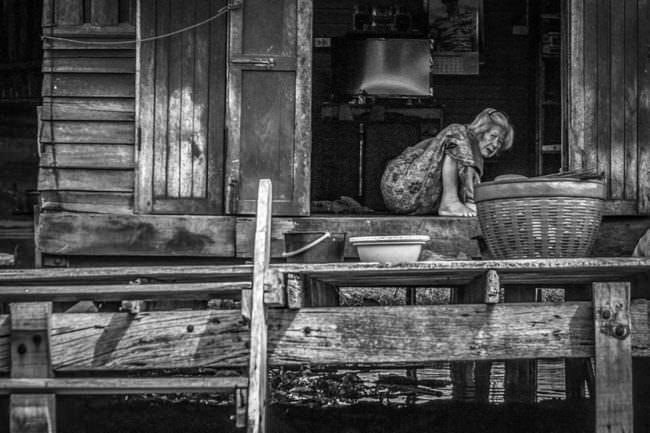 Eine Frau hockt auf dem Boden einer Hütte
