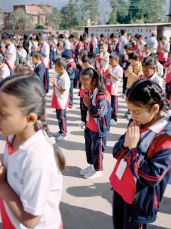 Kinder stehen auf einem Platz und falten die Hände