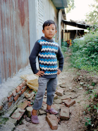 Ein Junge posiert vor einer Hauswand