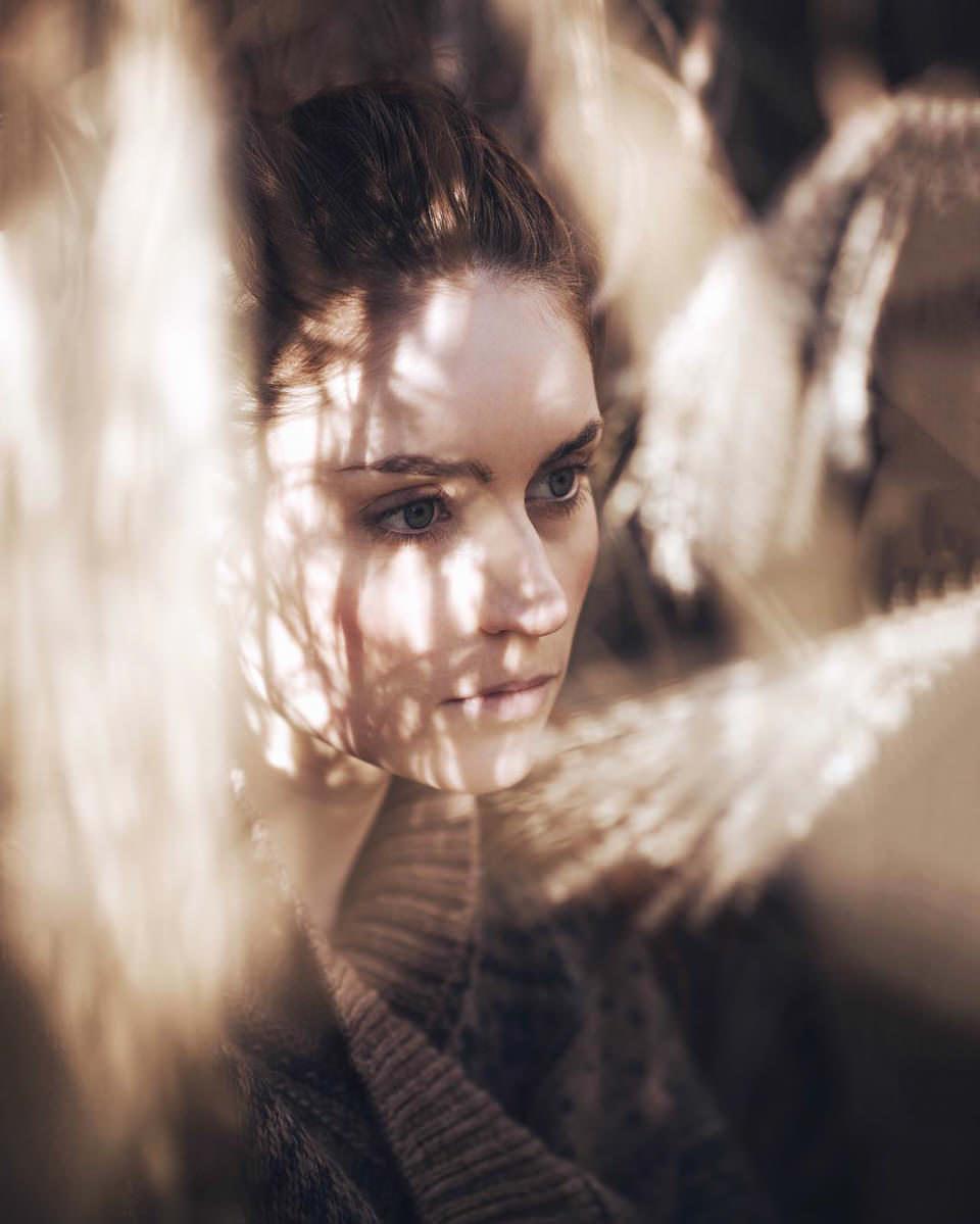 Portrait einer jungen Frau, auf deren Gesicht die Sonne scheint