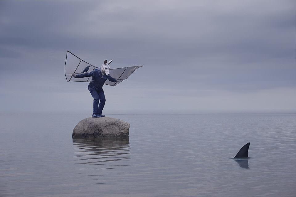 Ein Mensch verkleidet als Tier mit Flügeln auf einem Stein im Wasser
