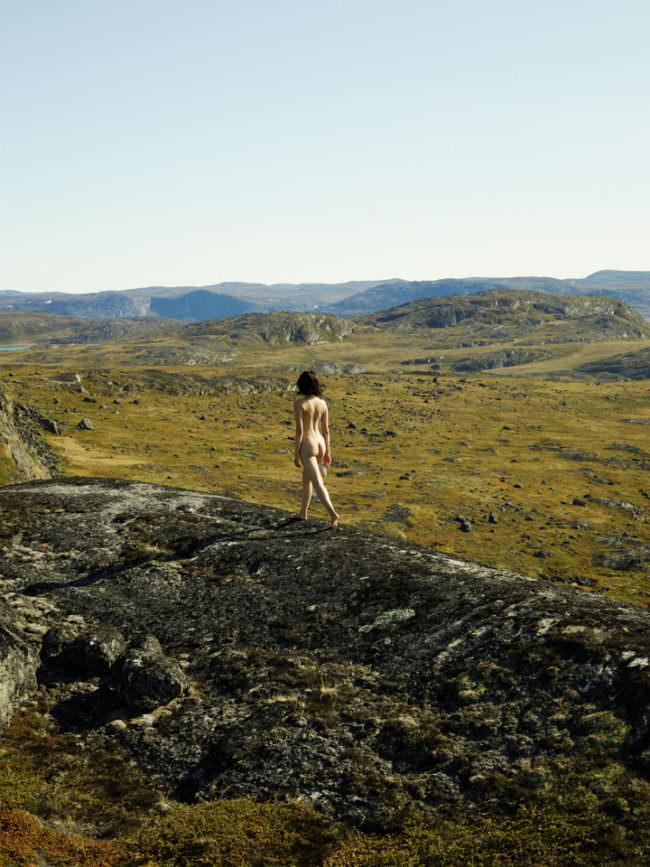 Eine Frau läuft nackt durch eine Landschaft