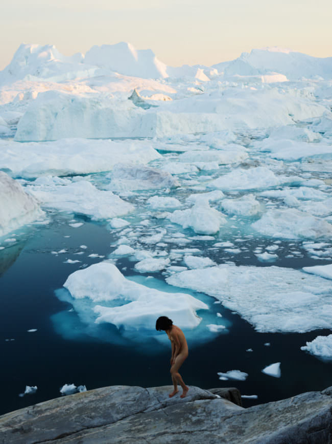 Eine nackte Frau läuft gebückt vor Eisschollen