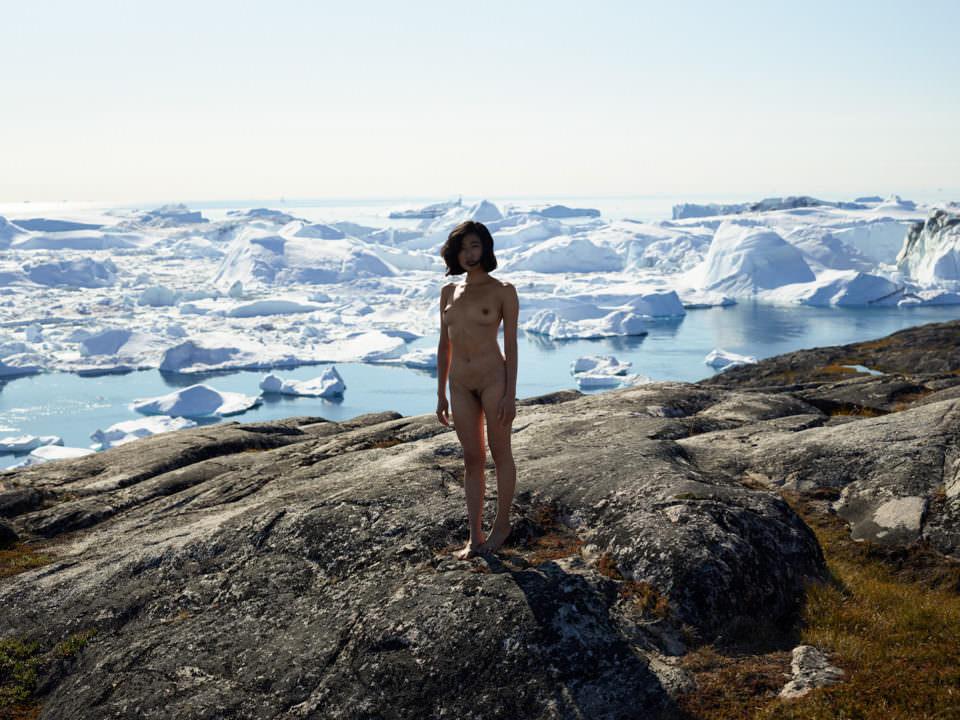 Eine nackte Frau steht vor Eisschollen