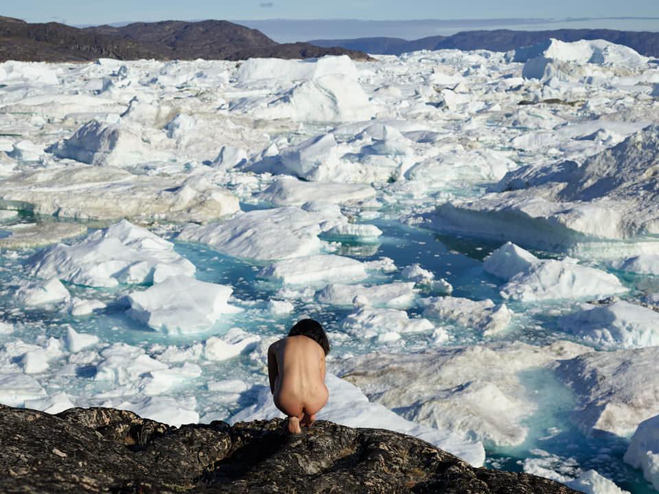 Eine nackte Frau hockt vor Eisschollen