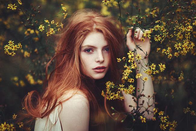 Eine Frau zwischen gelben Blüten