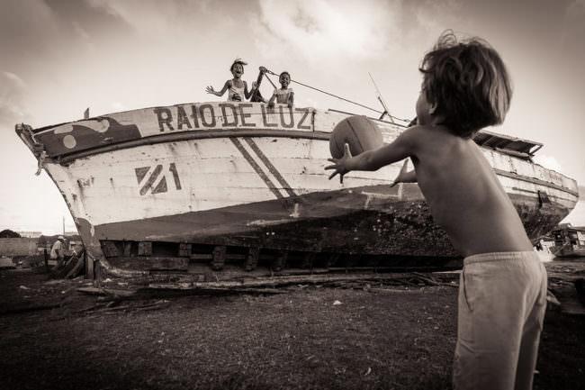Zwei Kinder spielen Ball von einem Boot aus