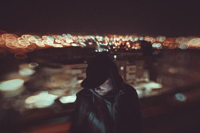 Ein Mann vor den nächtlichen Lichtern einer Stadt
