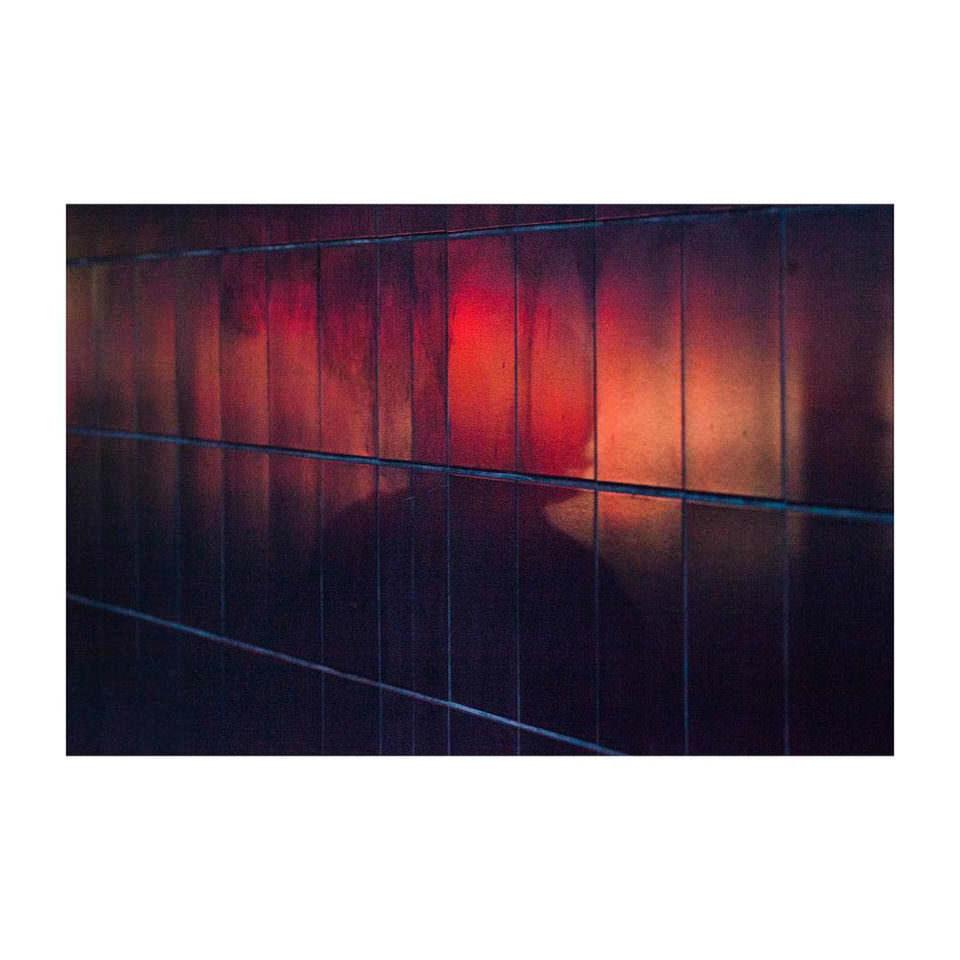 Rotes Licht strömt aus einem Fenster, in dem eine Silhouette zu erkennen ist