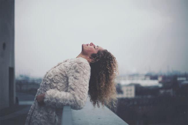 Eine Frau lehnt sich auf einem Balkon nach hinten