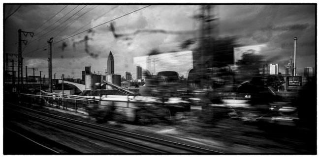 Schwarzweißfoto einer verwischten Stadtlandschaft.