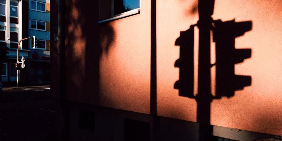 Schatten einer Ampel, der auf ein rotes Haus fällt.