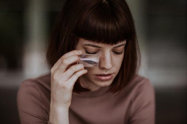 Eine Frau mit Prisma vor dem Auge