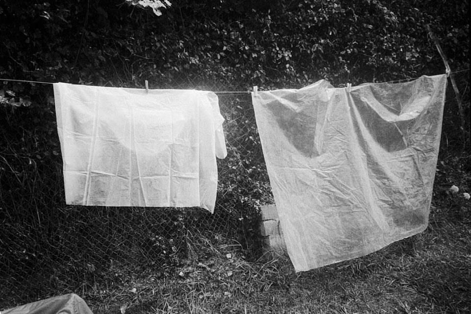 Schwarzweißaufnahme von 2 weißen Laken auf einer Wäscheleine im Grünen.