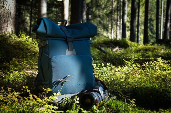 Ein Rucksack in einem Wald, vor der eine Kamera liegt.