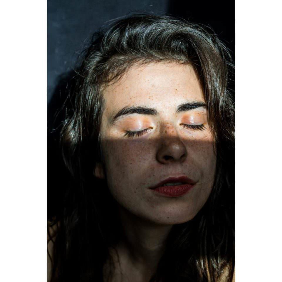 Nahaufnahme eines Frauengesichts mit dunklen Haaren und geschlossenen Augen, welches auf der oberen Hälfte lichtbeschienen ist.