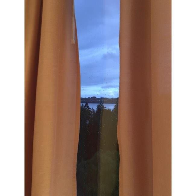 Blick aus einem Fenster durch einen Vorhangschlitz. Der orangefarbene Vorhang ist links und rechts sichtbar.