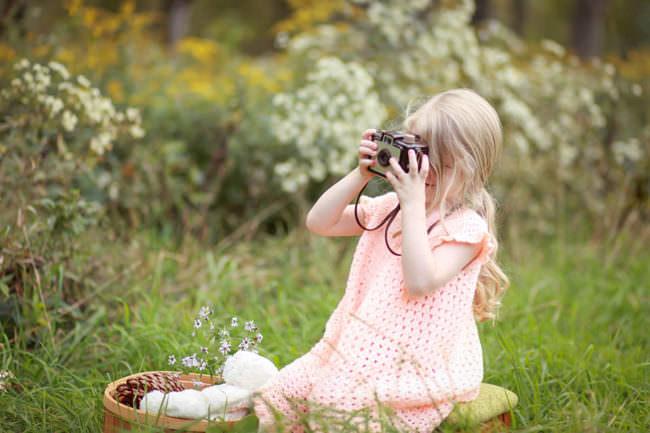 Ein Mädchen mit Kamera auf einer Wiese
