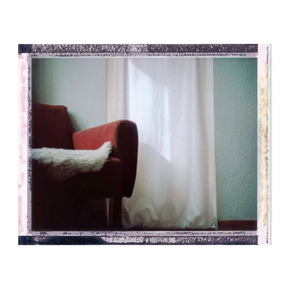 Polaroid einer roten Couch im Sonnenlicht