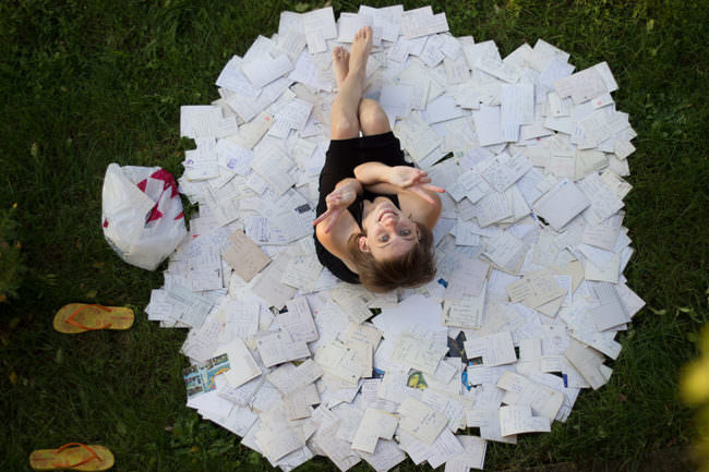 Eine Frau sitzt zwischen Postkarten