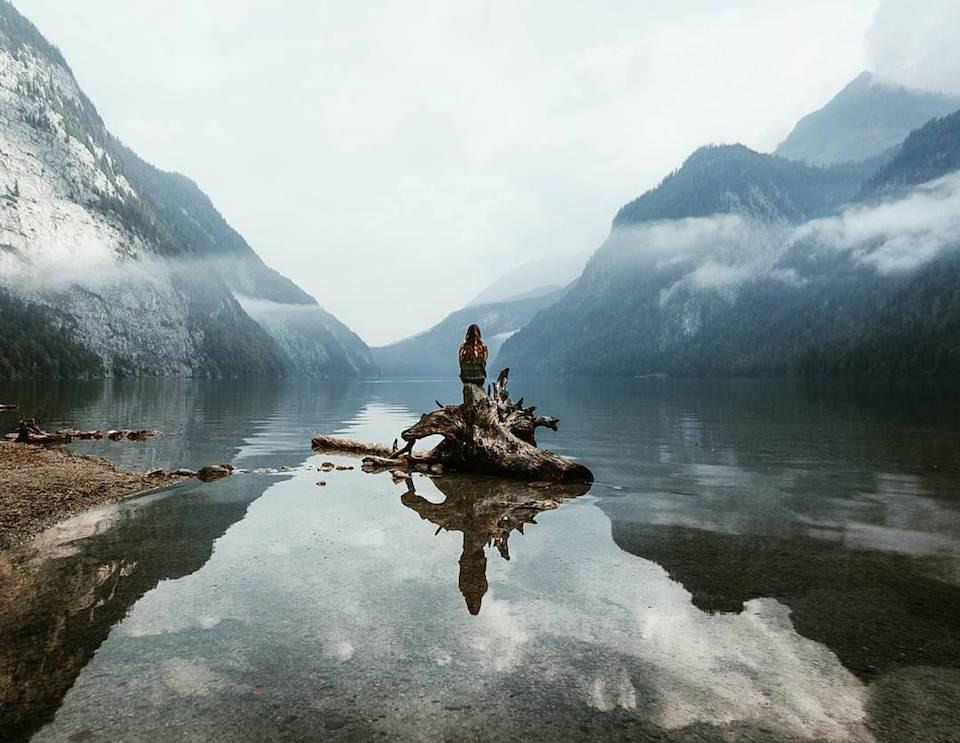 Ein Mensch der auf einem Baumstamm in einem See sitzt.