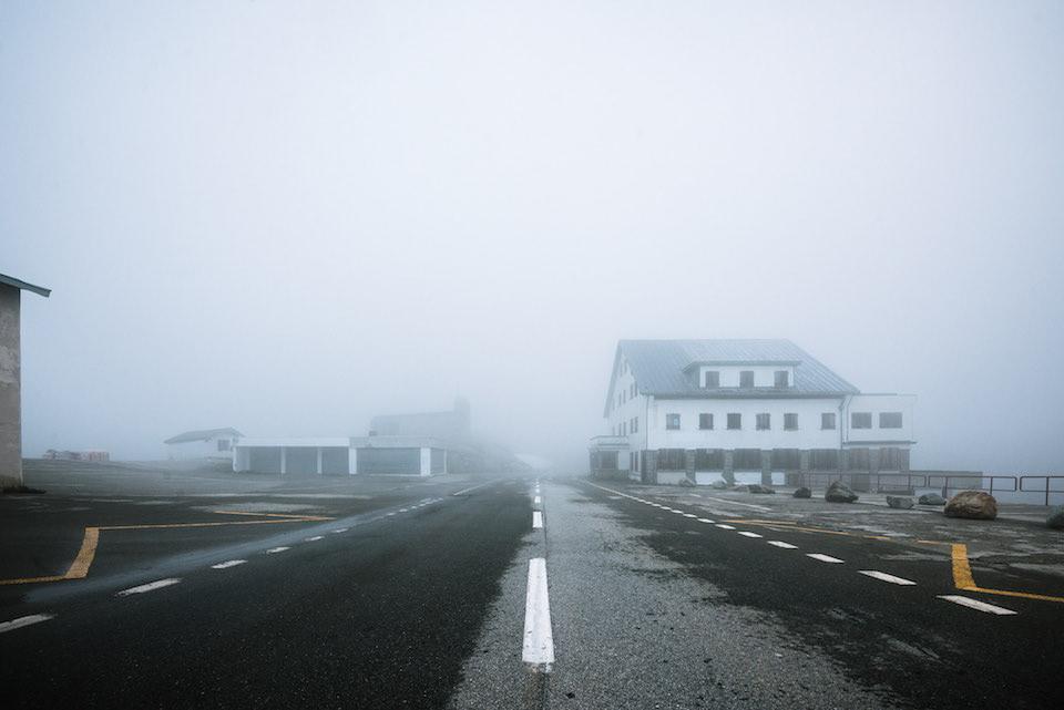 Eine Straße mit Häusern auf beiden Seiten, die in den Nebel führt.