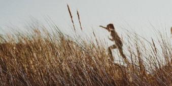 Ein Mensch der hinter Grashalmen einen Hügel hinaufläuft.