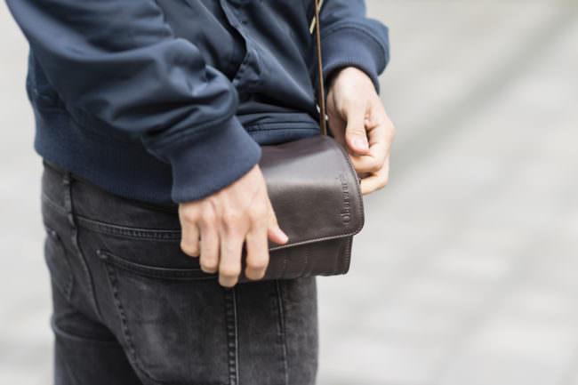 Ein Kameraholster, das an einem Gürtel hängt und von zwei Händen berührt wird.