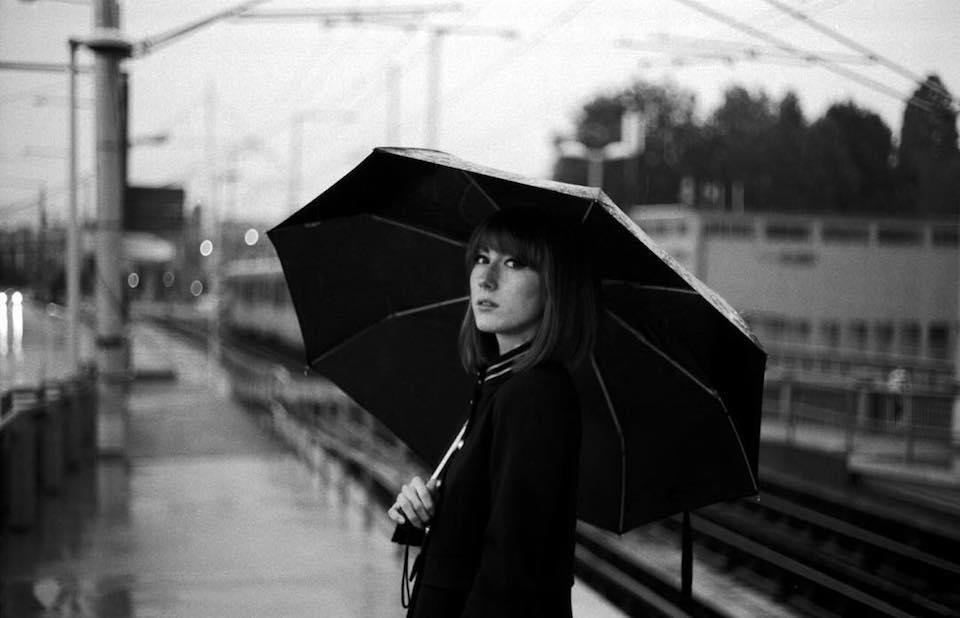 Eine Frau mit einem Schirm blickt nach hinten in die Kamera.