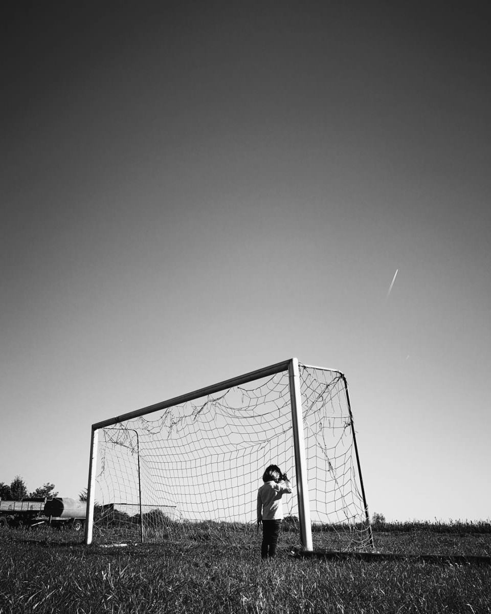 Kind in einem Fußballtor von hinten zu sehen in schwarzweiß.