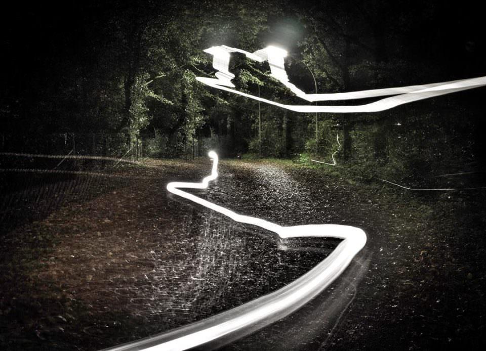 Lichtspuren auf einer nächtlichen Waldstraße.