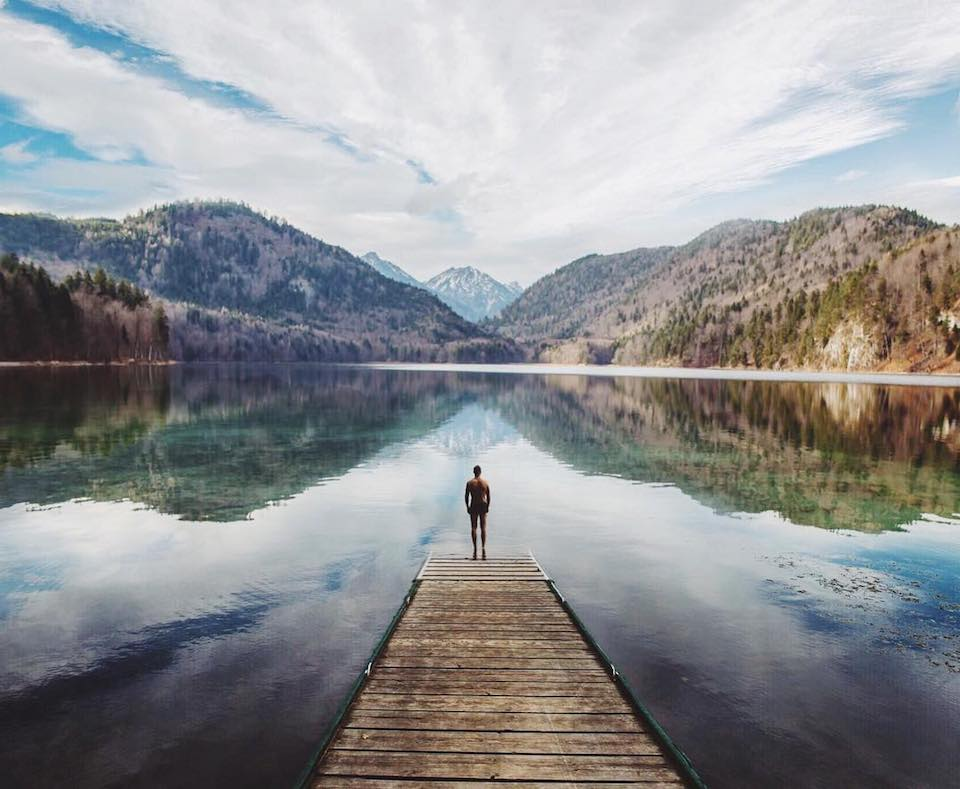 Ein Mensch der auf einem Steg auf einem Bergsee steht.
