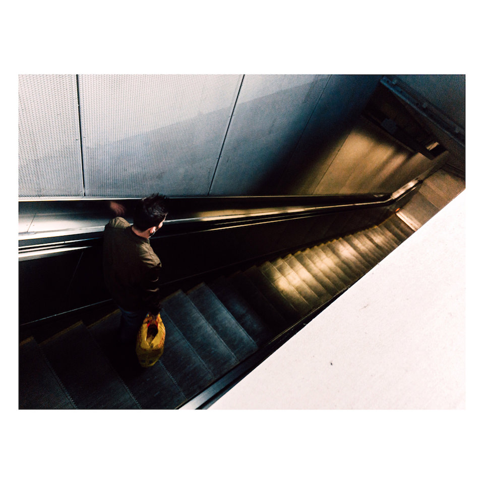 Ein Mann fährt eine Rolltreppe nach unten.