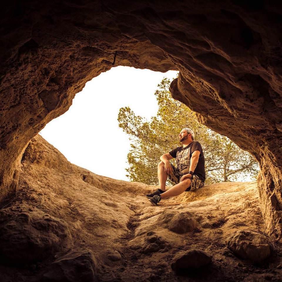 Ein Mann sitzt am Eingang zu einer Höhle, die nach unten führt.