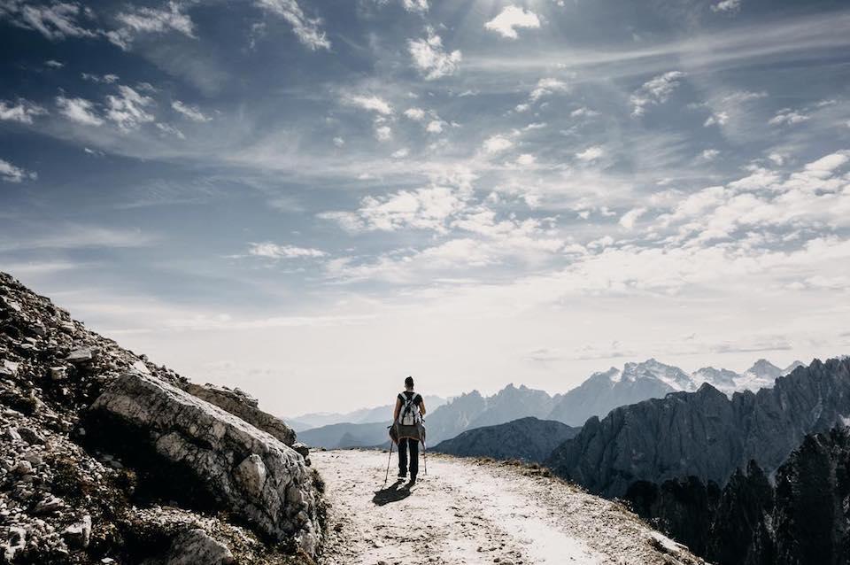 Ein Mensch der vor einem Bergpanorama wandert.