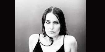 Frau in schwarzem Badeanzug liegend auf einer Holzplanke mit Blick zum Betrachter. Das Foto ist schwarzweiß.