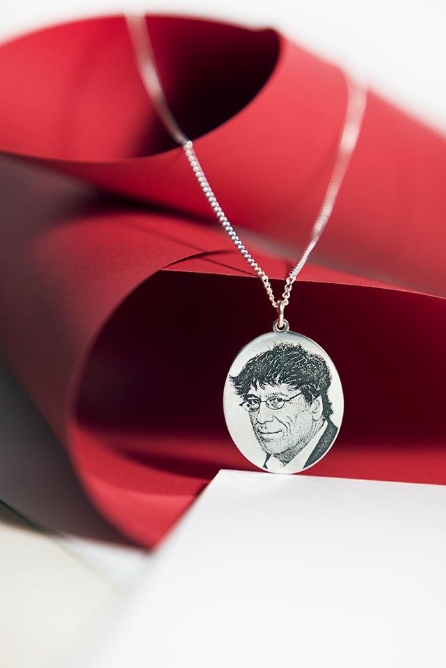 Fotogravurkette in Silber mit einem Portrait arrangiert mit roten Papierrollen.