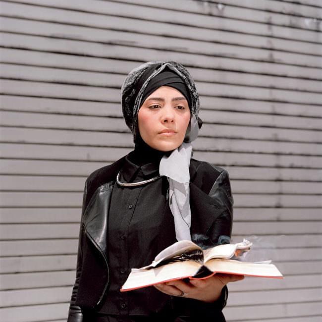 Eine Frau mit ernstem Gesichtsausdruck, Kopftuch und brennendem Buch in der Hand