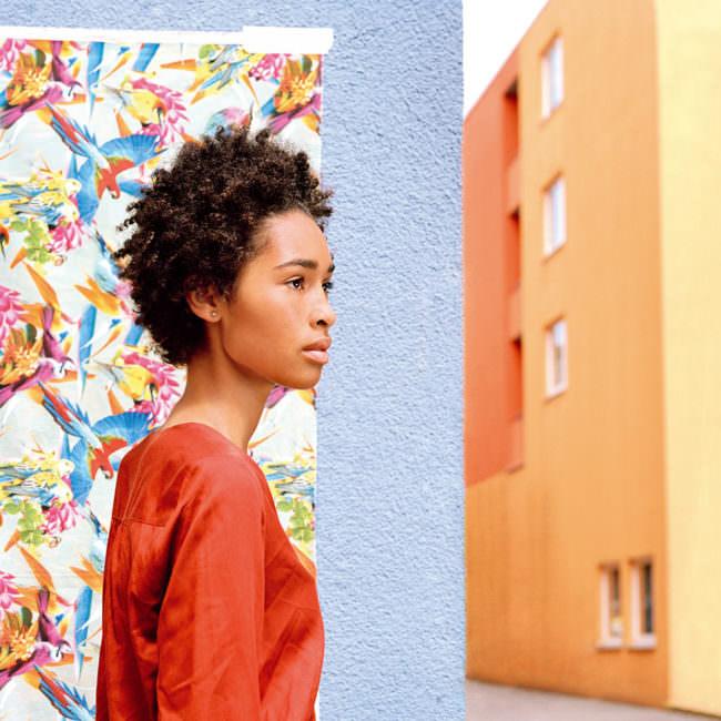 Eine Frau vor einer Blumenwand und bunten Hauswänden
