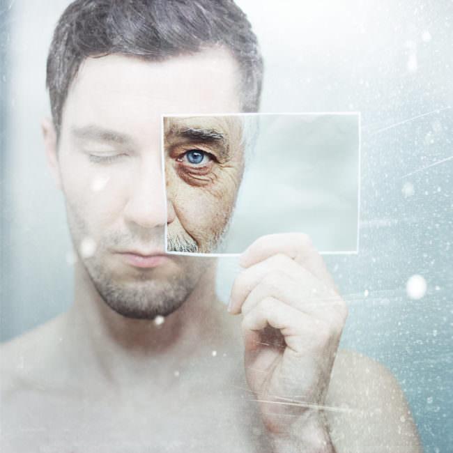 Foto eines jungen Mannes, der sich ein Foto eines älteren Mannes vor das Auge hält
