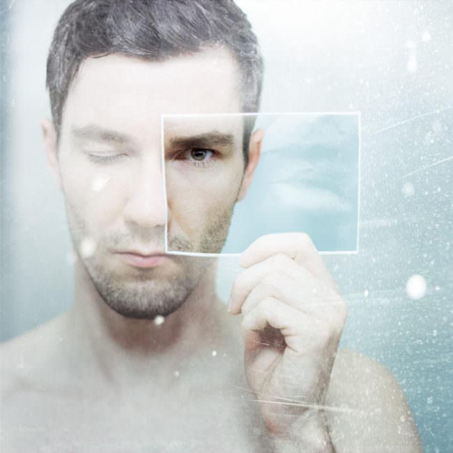 Mann mit geschlossenem Augen hält ein Bild seines offenen Auges vor sein Gesicht