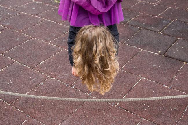 Ein Kind hängt mit dem Kopf nach unten