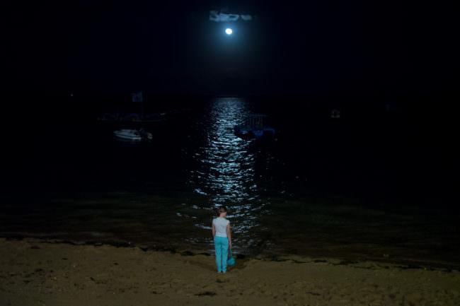 Ein Kind in der Nacht vor einem Gewässer