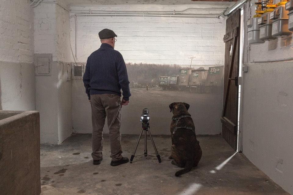Ein Mann mit Hund steht vor einer beluchteten Wand