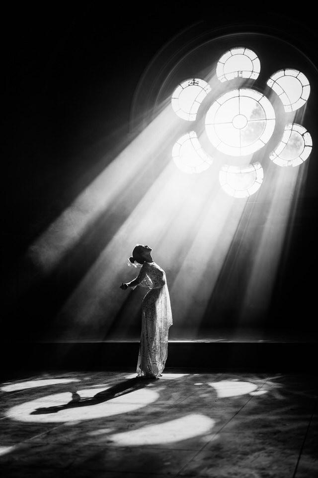 Eine Frau vor einem Fenster, durch das das Licht fällt