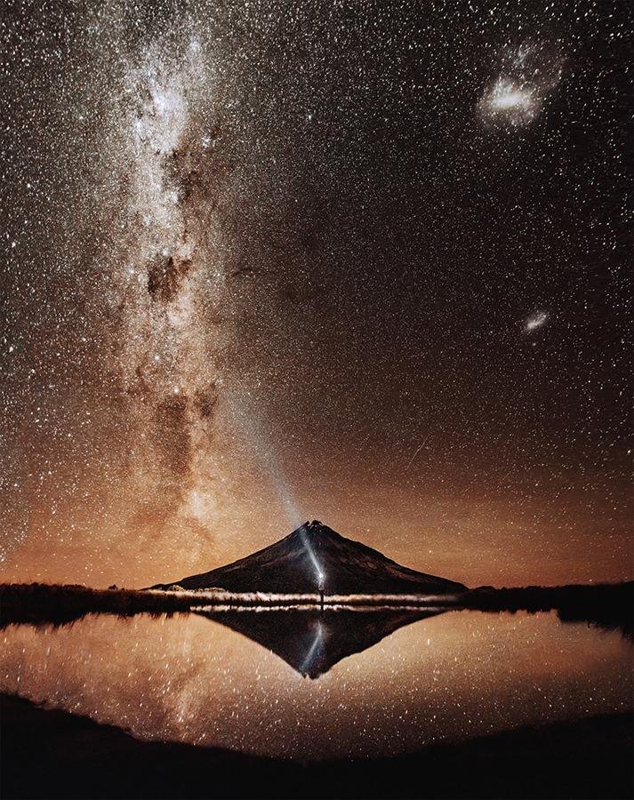 Eine Person mit Taschenlampe scheint in den Nachthimmel